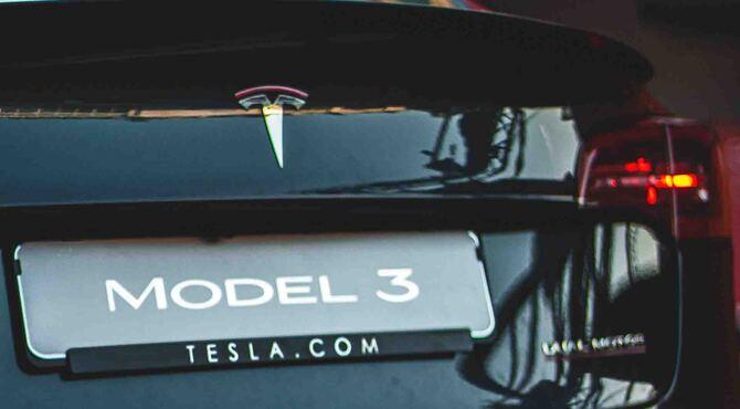 Vizual zadnjeg dela crnog automobila model Tesla 3