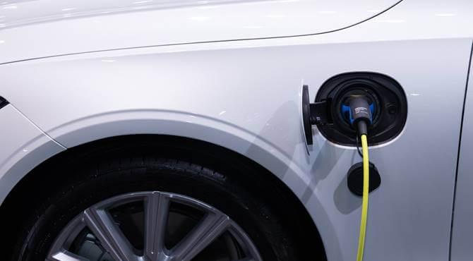 beli električni automobil na punjaču